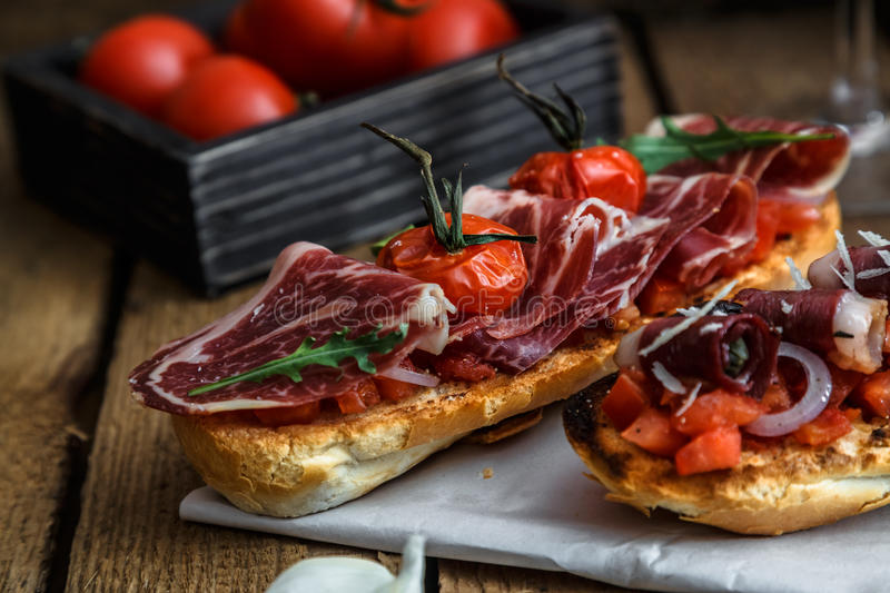 Closeup shot of an bruschetta with tomatoes salsa, parma, arugula and olives, close view stock photos