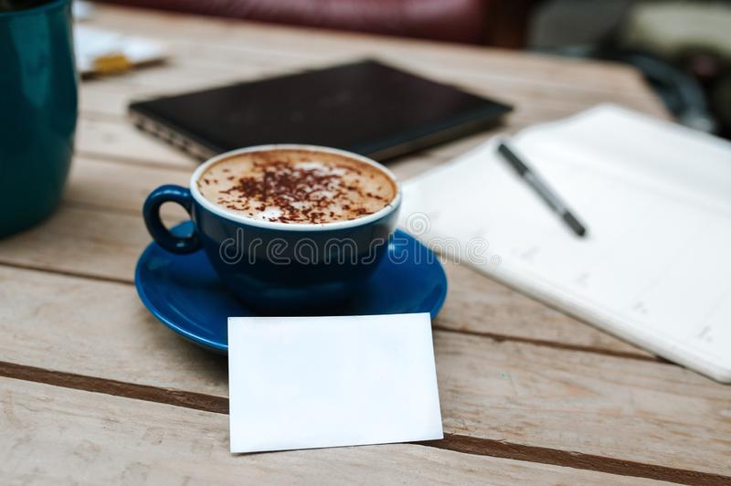 Closeup shot of cappuccino in a blue ceramic cup, a black tablet and notebook on the table. A closeup shot of cappuccino in a blue ceramic cup, a black tablet royalty free stock images