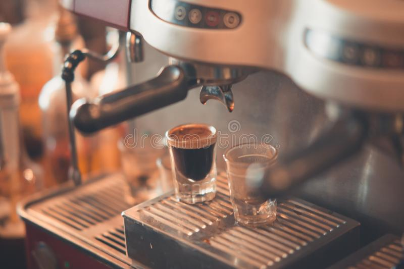 Closeup shot of coffee cups on an espresso machine drip tray royalty free stock image