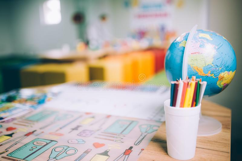 Closeup shot of colorful pencils in a cup and a globe on a table at a daycare center. A closeup shot of colorful pencils in a cup and a globe on a table at a royalty free stock photography