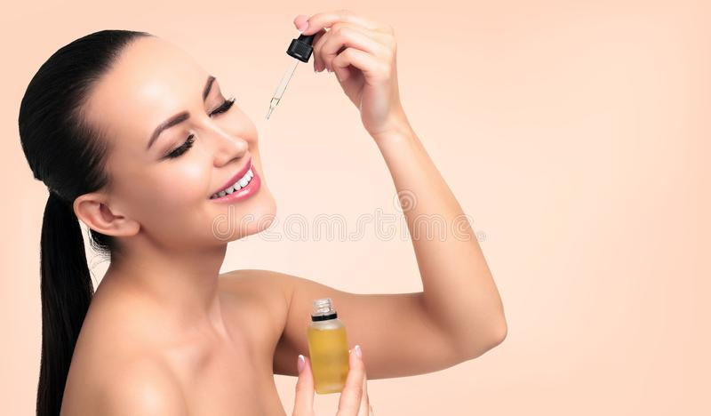 Closeup shot of cosmetic oil applying on young woman`s face stock photography