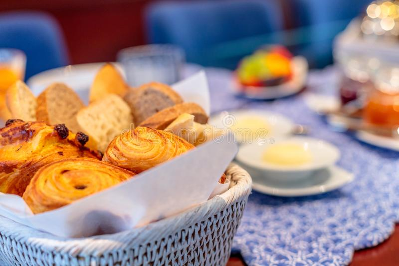 Closeup shot of croissants and other pastry in a basket on a blurred breakfast table stock image