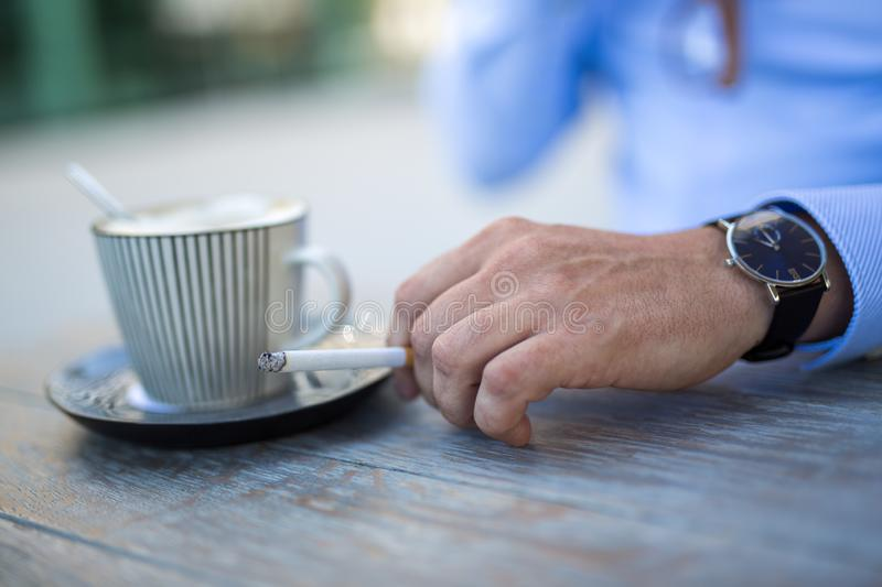 Closeup shot of a cup of coffee and a mans hand with a cigarette royalty free stock photo