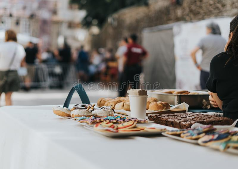 Closeup shot of different types of sweet and delicious goods on a table. A closeup shot of different types of sweet and delicious goods on a table with people royalty free stock image