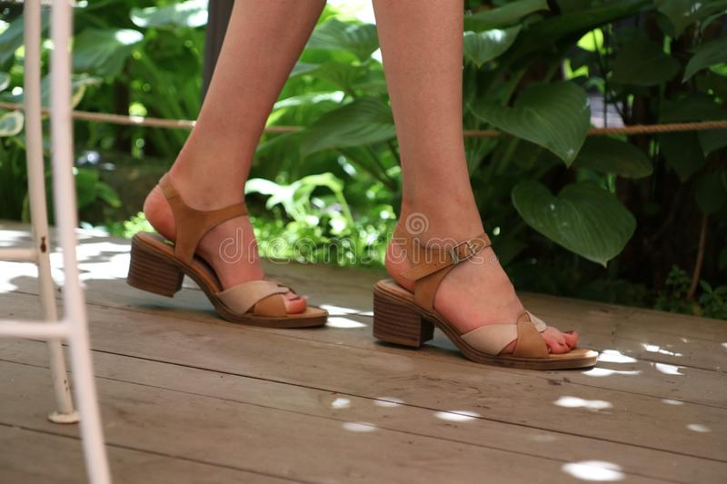 Closeup shot of elegant feet of a female walking on a wooden surface royalty free stock photos