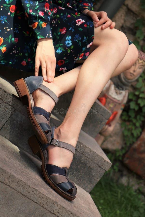 Closeup shot of elegant feet of a female wearing a dress at Summer stock photo
