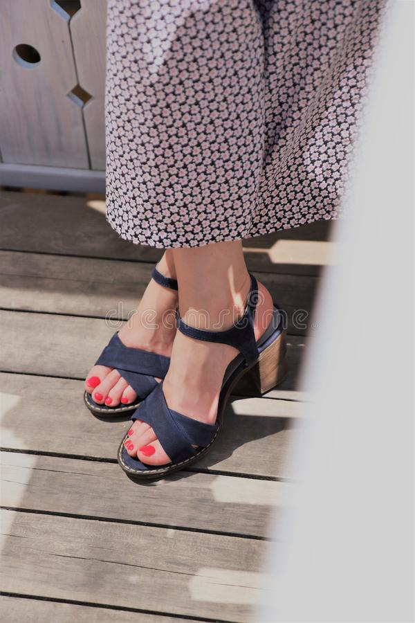 Closeup shot of elegant feet of a female wearing a dress at Summer royalty free stock photography