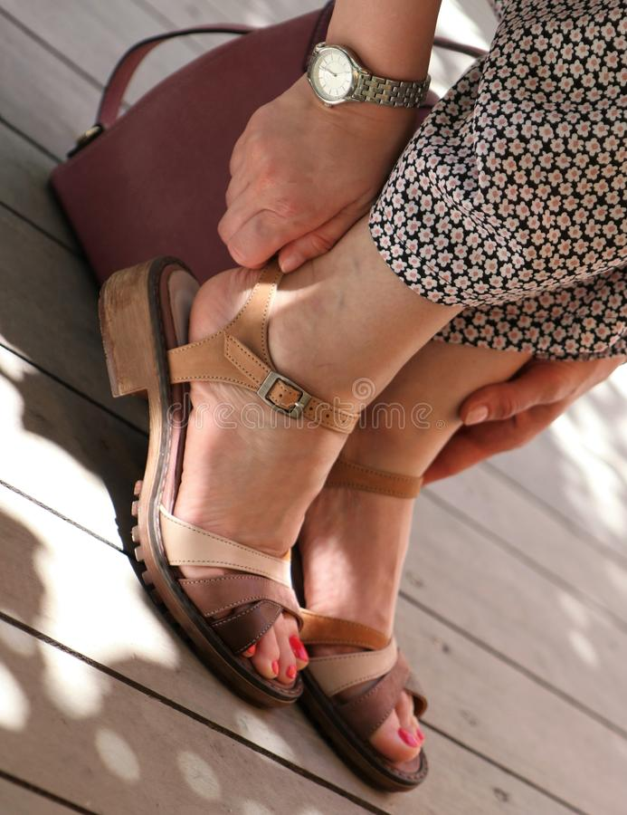 Closeup shot of elegant feet of a female wearing a dress at Summer stock photography