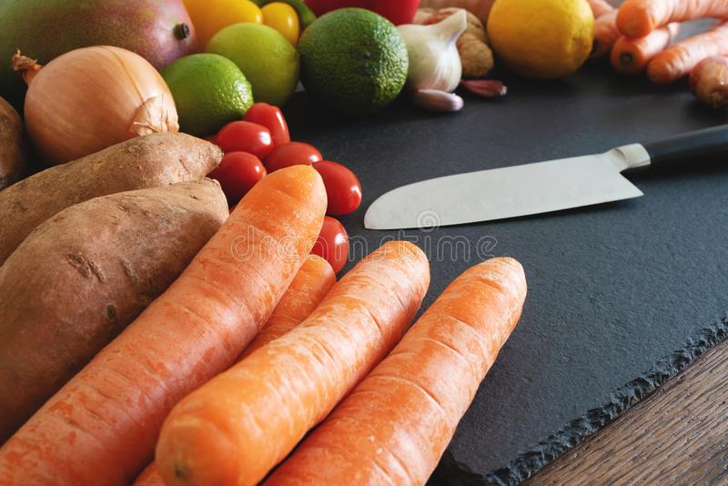 Fresh organic fruits and vegetables on slate cutting board with kitchen knife royalty free stock image