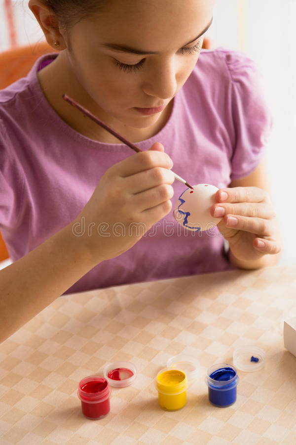 Closeup shot of girl painting pattern on Easter egg. Closeup photo of girl painting pattern on Easter egg royalty free stock images
