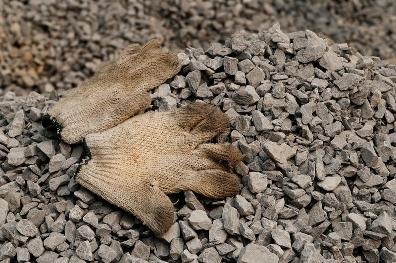 Closeup shot of glove and gravel black rock on construction site for background. Construction is the process of constructing a bui. Lding or infrastructure royalty free stock photo