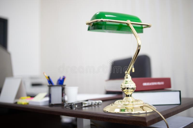 Closeup shot of a green desktop lamp at an office with books and files. A closeup shot of a green desktop lamp at an office with books and files royalty free stock image