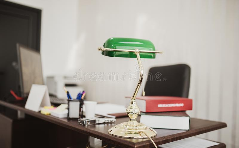Closeup shot of a green desktop lamp at an office with books and files. A closeup shot of a green desktop lamp at an office with books and files royalty free stock images