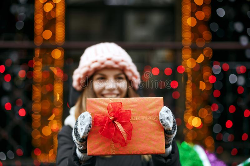 Closeup shot of happy blonde woman holding gift box. Blurred bokeh background. Space for text stock image
