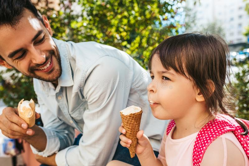 Closeup shot of happy cute little girl sitting with handsome dad on the city street and eating ice-cream outdoor. Fun girl kid and royalty free stock image