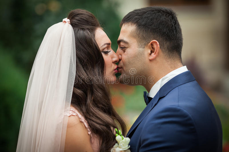 Closeup shot of happy newlywed couple kissing stock photography