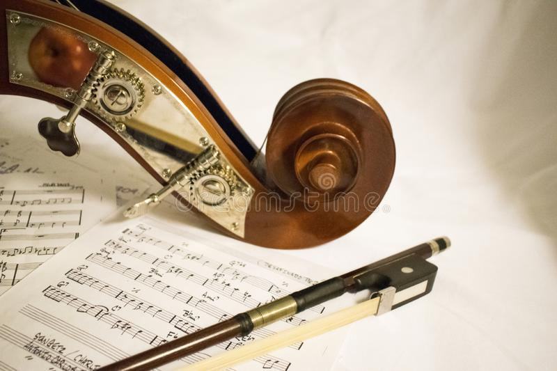 Closeup shot of the headstock of a violin and the string on a paper of notes royalty free stock photo