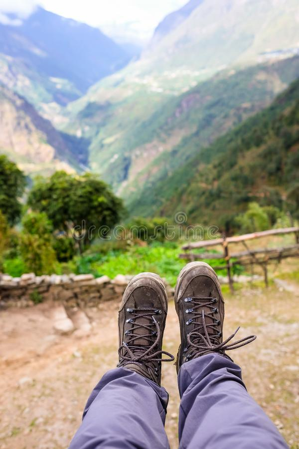 Closeup shot of hiker`s legs with brown colored hiking boots with mountains on the background in Himalayas royalty free stock images
