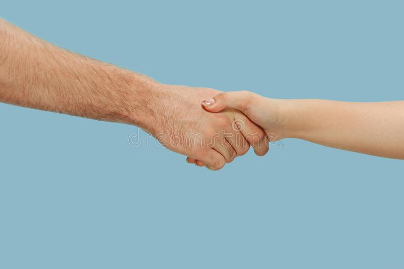 Closeup shot of human holding hands isolated on blue studio background. Concept of human relations, friendship, partnership, family. Copyspace stock photos