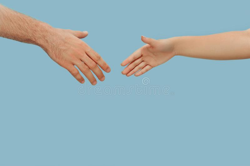 Closeup shot of human holding hands isolated on blue studio background. Concept of human relations, friendship, partnership, family. Copyspace royalty free stock photos