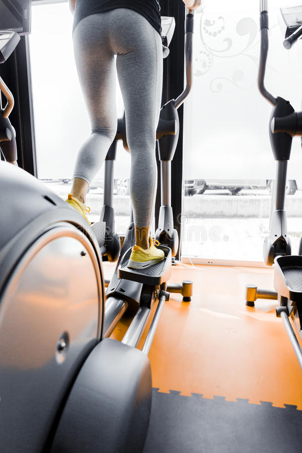 Closeup shot of legs of a female using elliptical trainer royalty free stock photo
