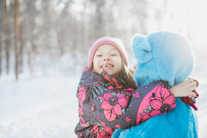 Closeup shot of a naturally smiling little girl in the arms of a female in a fluffy blue costume royalty free stock images