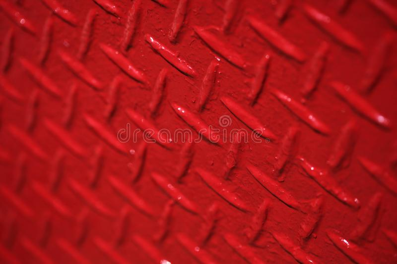 Closeup shot of a painted red metal texture with unique patterns as a beautiful background. A closeup shot of a painted red metal texture with unique patterns as stock images