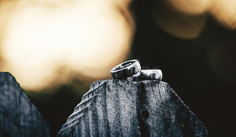 Let No One Put Asunder. Closeup shot of a pair of tungsten wedding rings set atop of a wooden slat with the sun setting behind them royalty free stock photography