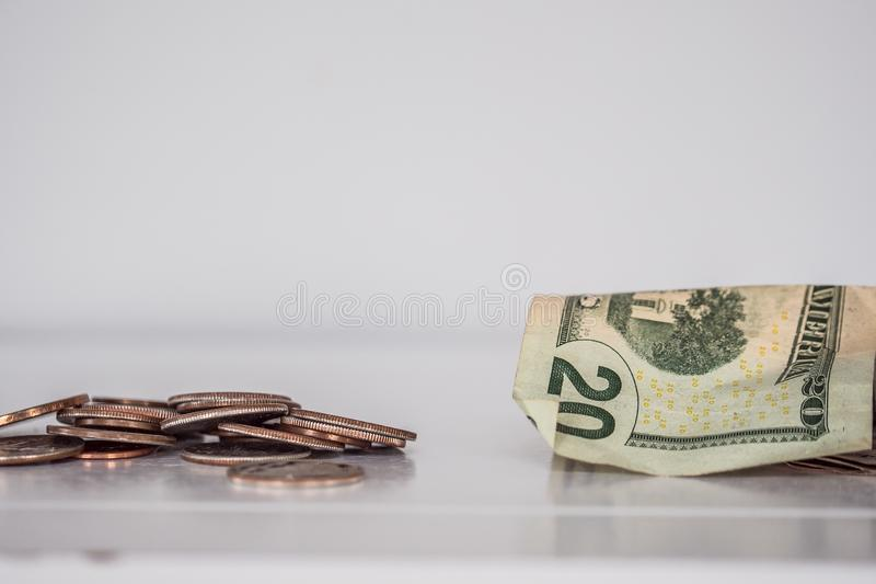 Closeup shot of pennies and a twenty-dollar bill on a white surface stock photo