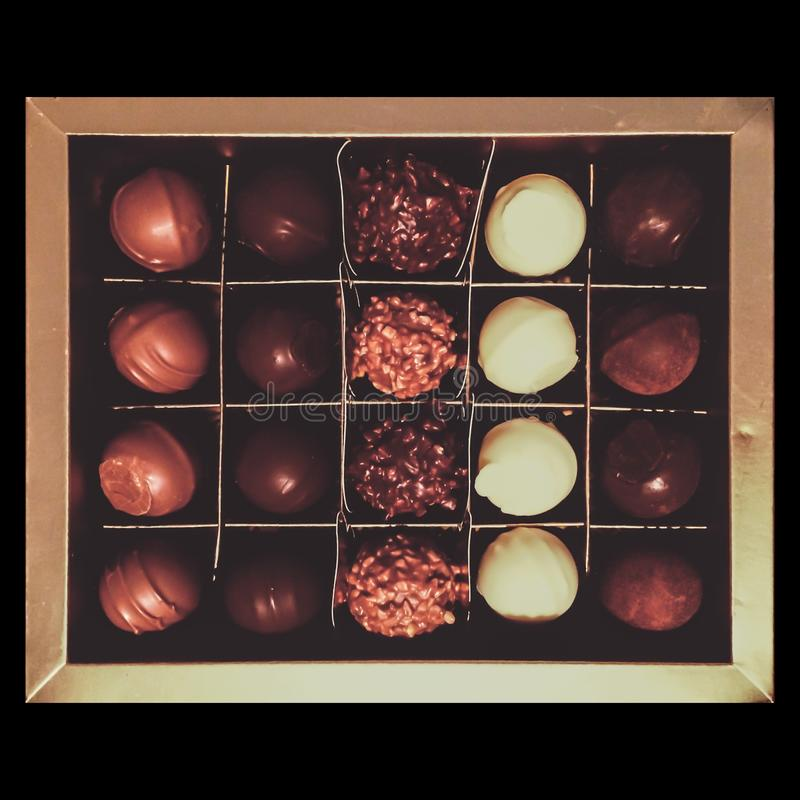 Overhead shot of a chocolate box full of white brown chocolate candies stock photo