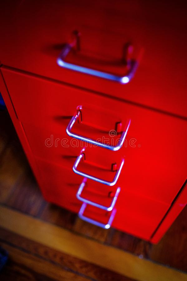 Closeup shot of a red cabinet on a wooden surface with metal handles. A closeup shot of a red cabinet on a wooden surface with metal handles royalty free stock photos