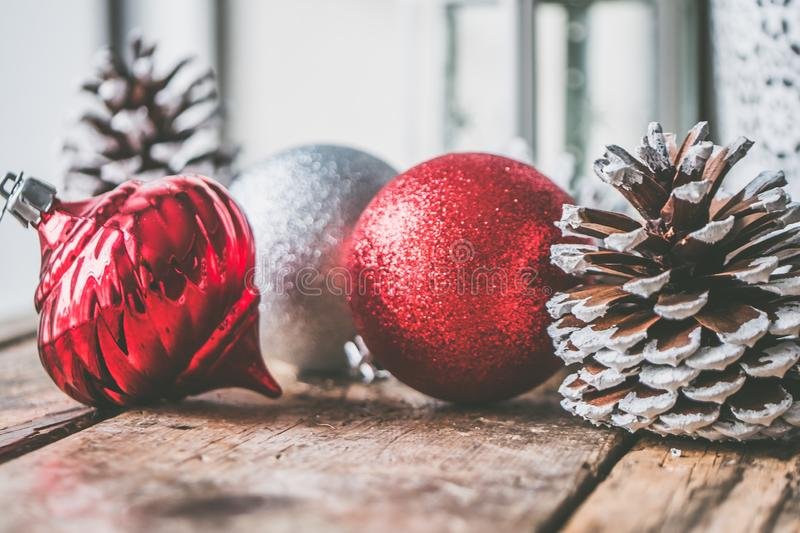 Closeup shot of red and gray Christmas decorations with pinecones on a wooden surface stock photos