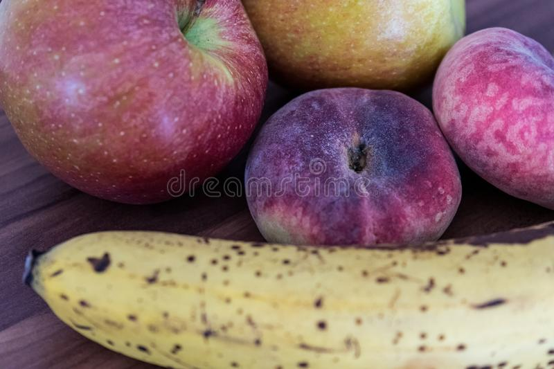 Closeup shot of Saturn peaches, bananas and apples on a wooden surface stock photos