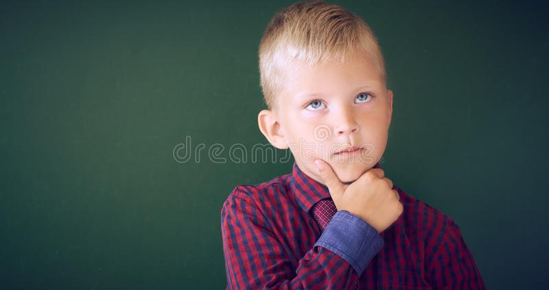 Closeup shot of schoolboy thinking with hand on chin isolated on blackboard. Portrait of pensive child thinking about royalty free stock images