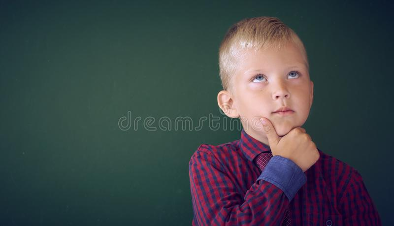 Closeup shot of schoolboy thinking with hand on chin isolated on blackboard. Portrait of pensive child thinking about royalty free stock photography