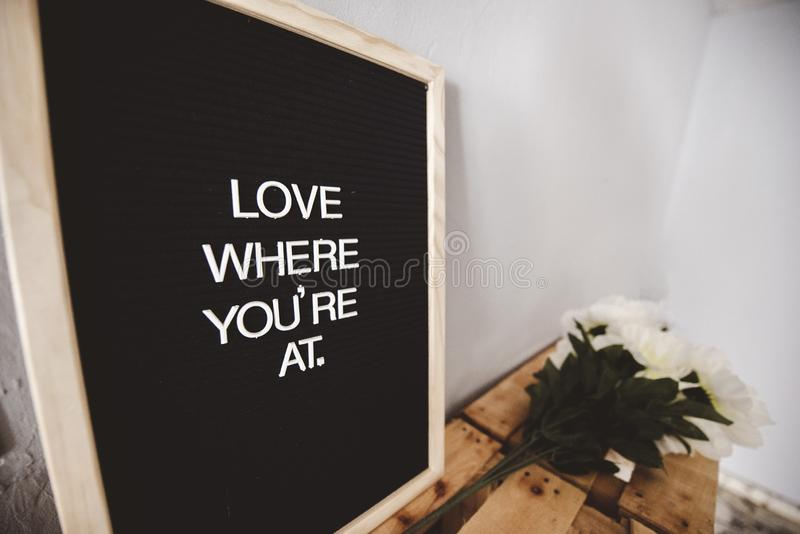 Closeup shot of a sign with love where you`re at written on it near a white flower royalty free stock image