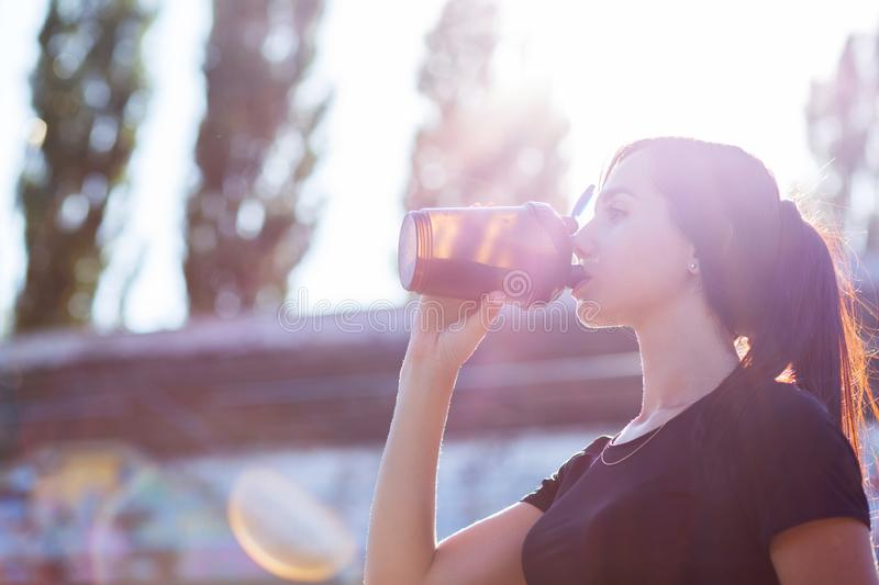 Closeup shot of sporty model drinking water in soft evening backlight. Empty space stock photography