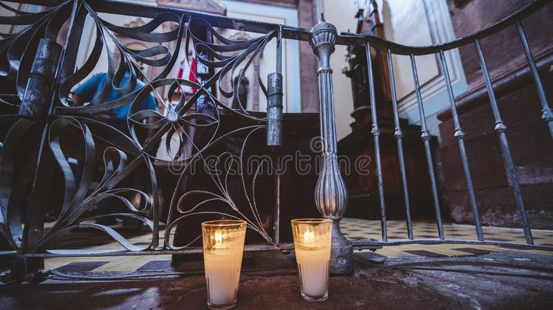 Closeup shot of two lit candles near a metal fence in the church with a blurred background royalty free stock images