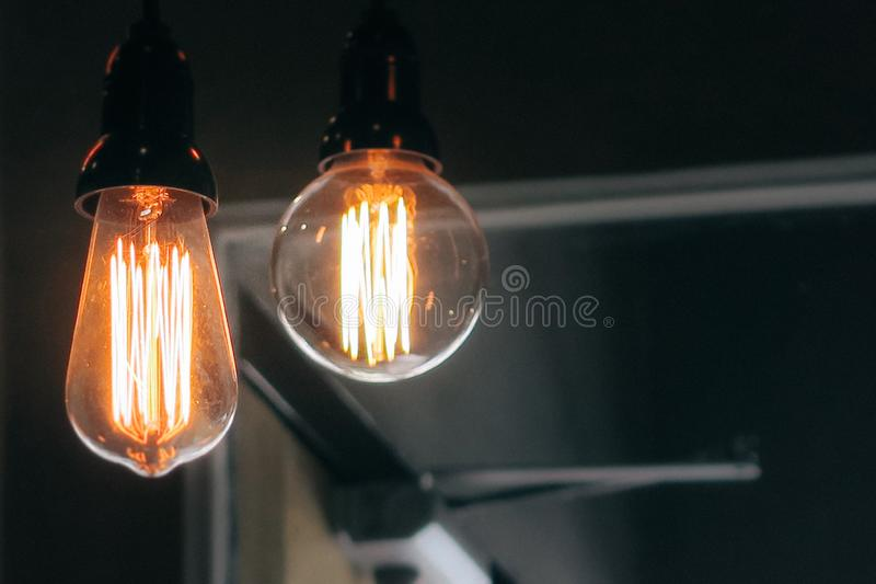 Closeup shot of two lit large lightbulbs on a dark background stock photography
