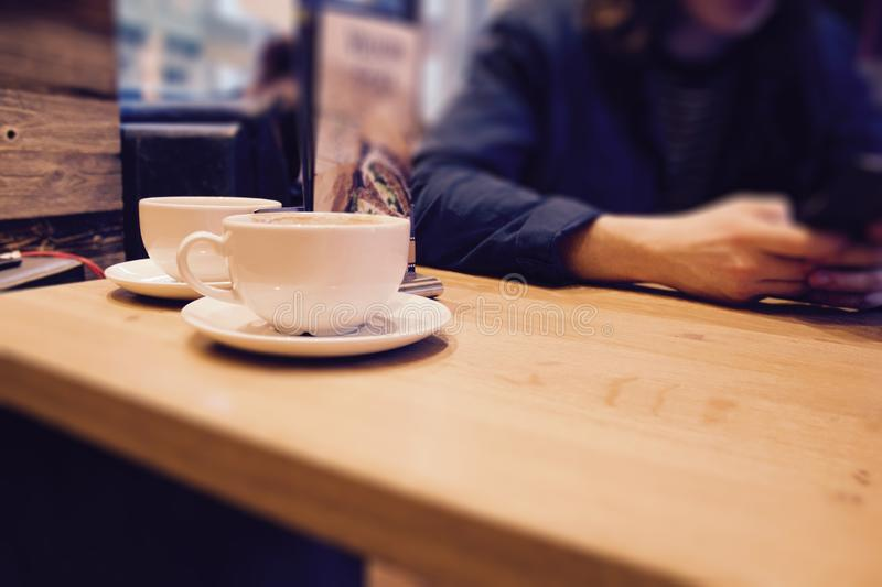 Closeup shot white cups of coffee on a wooden surface with a person sitting by at a cafe. A closeup shot white cups of coffee on a wooden surface with a person royalty free stock photos