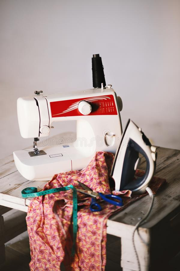 Closeup shot of a white sewing machine, textile, scissors, measuring tape and iron on a table stock image