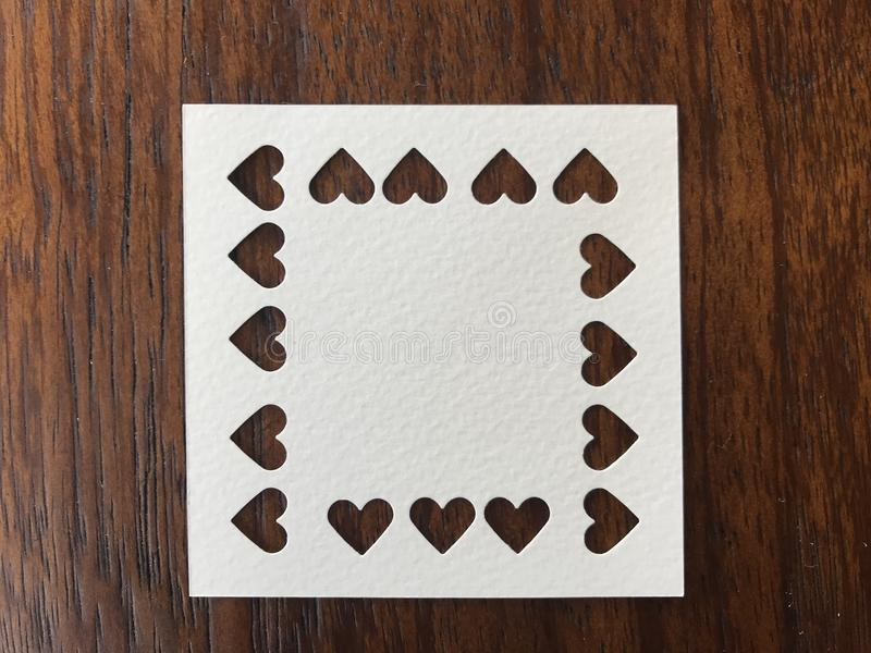 Closeup shot of white square blank paper which was punched in heart shape royalty free stock photo