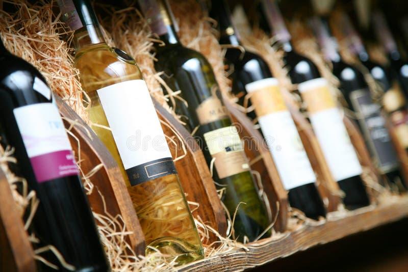Closeup shot of wineshelf. Bottles lay over straw royalty free stock photos