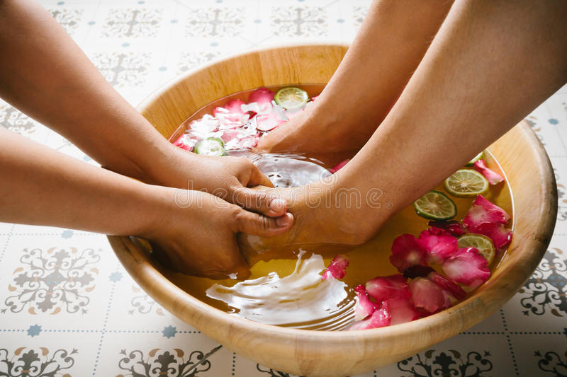 Closeup shot of a woman feet dipped in water with petals in a wooden bowl. Beautiful female feet at spa salon on pedicure procedure. Shallow depth of field stock photography