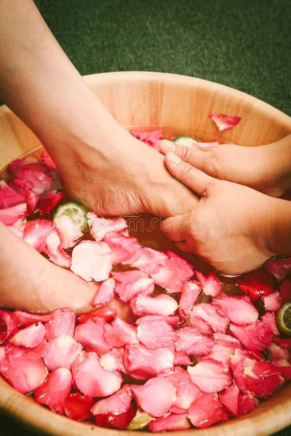 Closeup shot of a woman feet dipped in water with petals in a wooden bowl. Beautiful female feet at spa salon on pedicure procedure. Shallow depth of field stock image