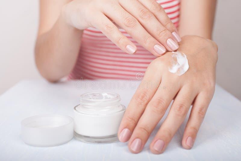 Closeup shot of woman hands applying moisturizing hand cream royalty free stock photo