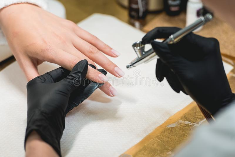 Closeup shot of a woman in a nail salon receiving a manicure by a beautician with airbrush. Woman getting nail manicure. stock photos