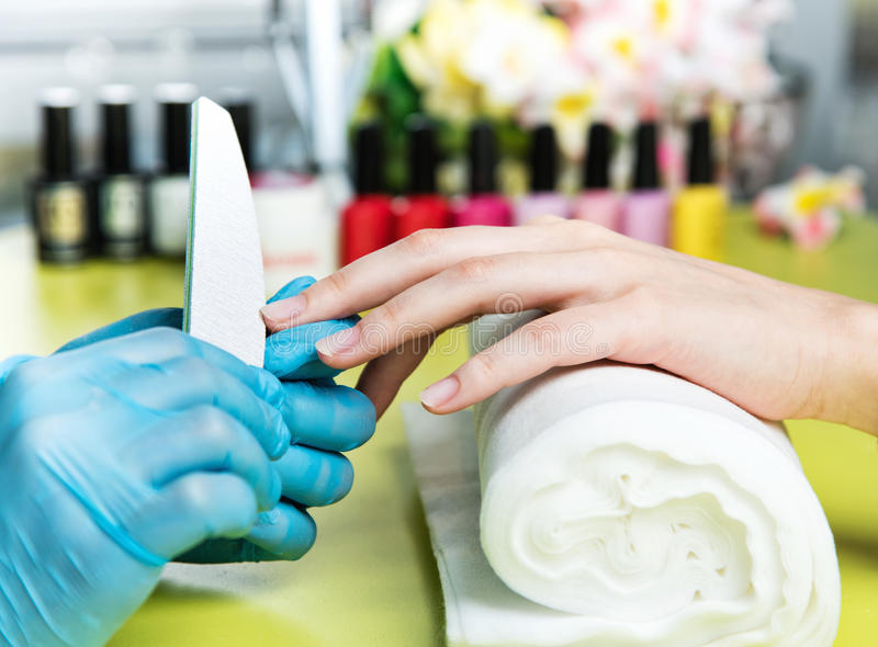Closeup shot of a woman in a nail salon receiving a manicure by a beautician with nail file. Woman getting nail manicure. Beautici royalty free stock photos