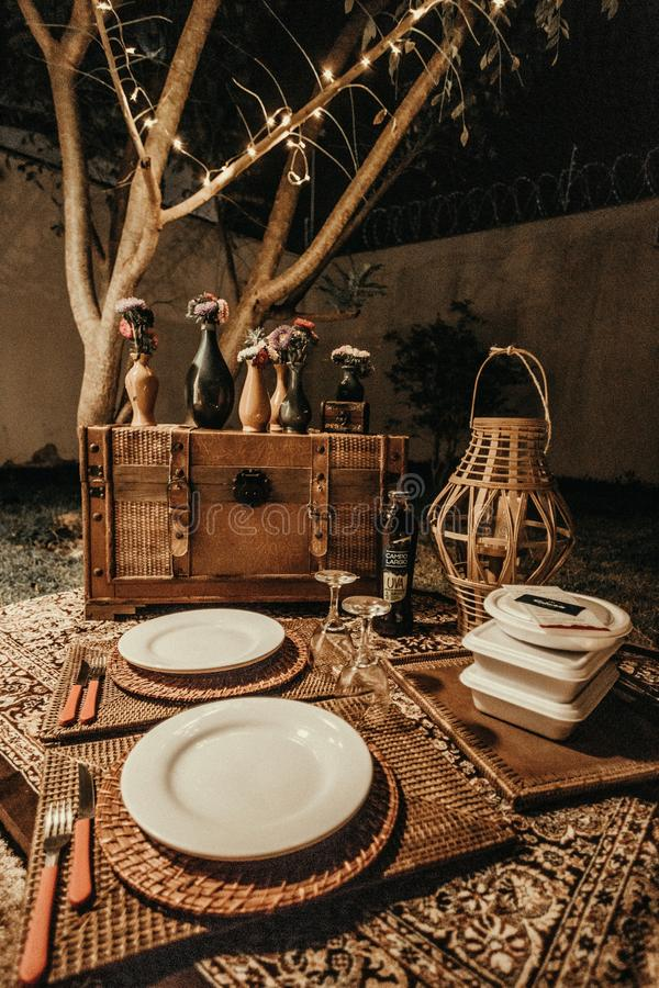 Closeup shot of a wooden chest, with vases on it, a straw basket, plates, and wine glasses. A closeup shot of a wooden chest, with vases on it, a straw basket stock images