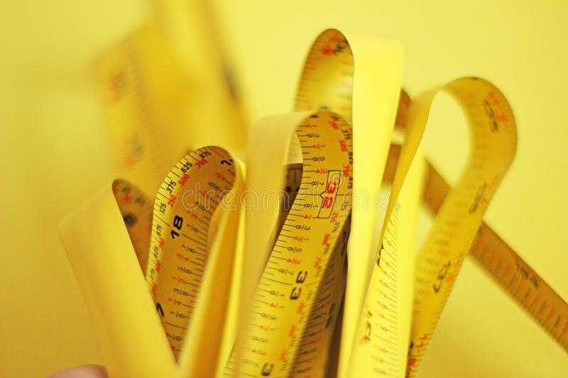 Closeup shot of yellow measurer or ruler on a yellow blurred background. A closeup shot of yellow measurer or ruler on a yellow blurred background royalty free stock images